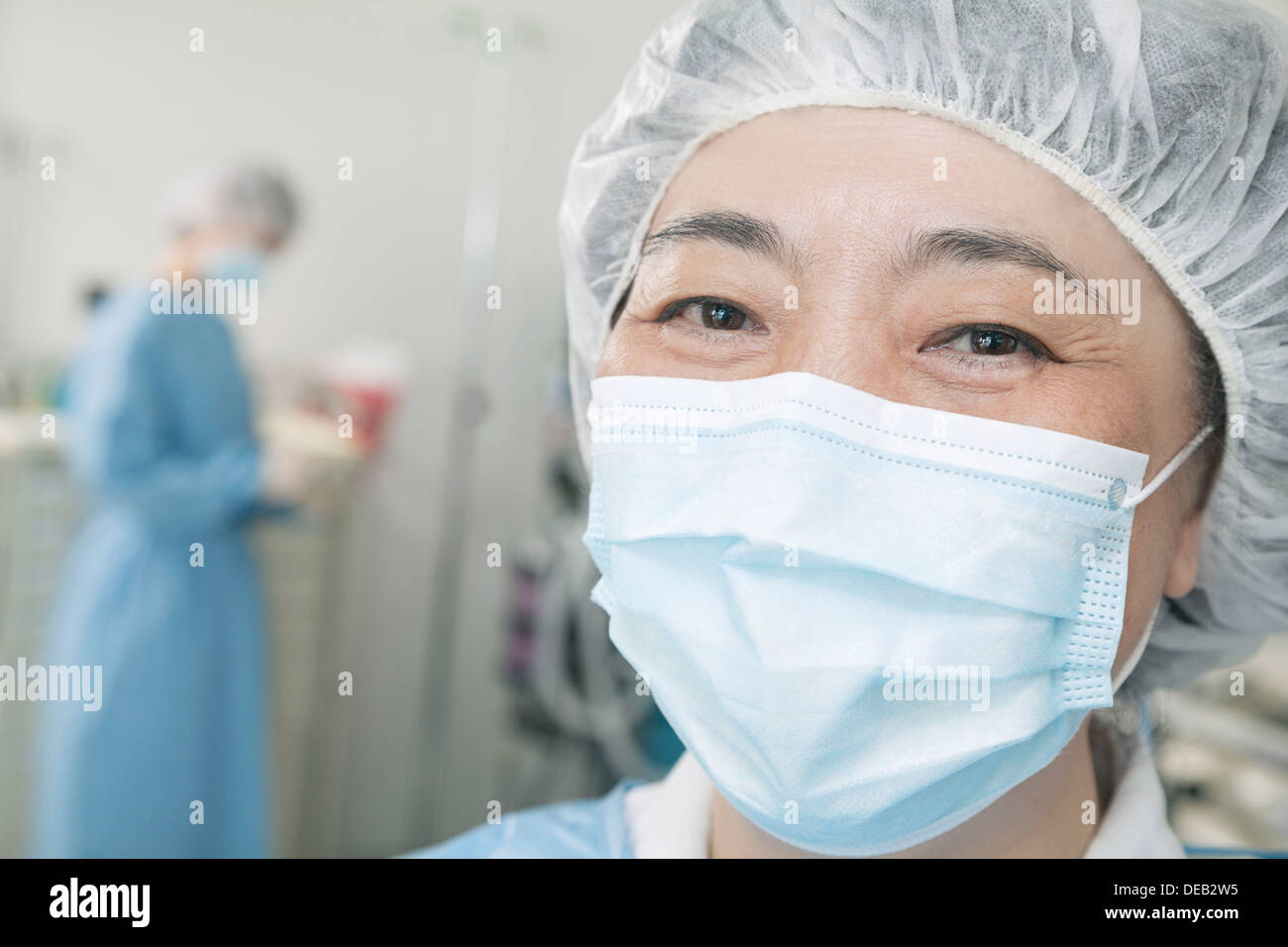 Portrait of surgeon with surgical mask and surgical cap in the operating room - Stock Image