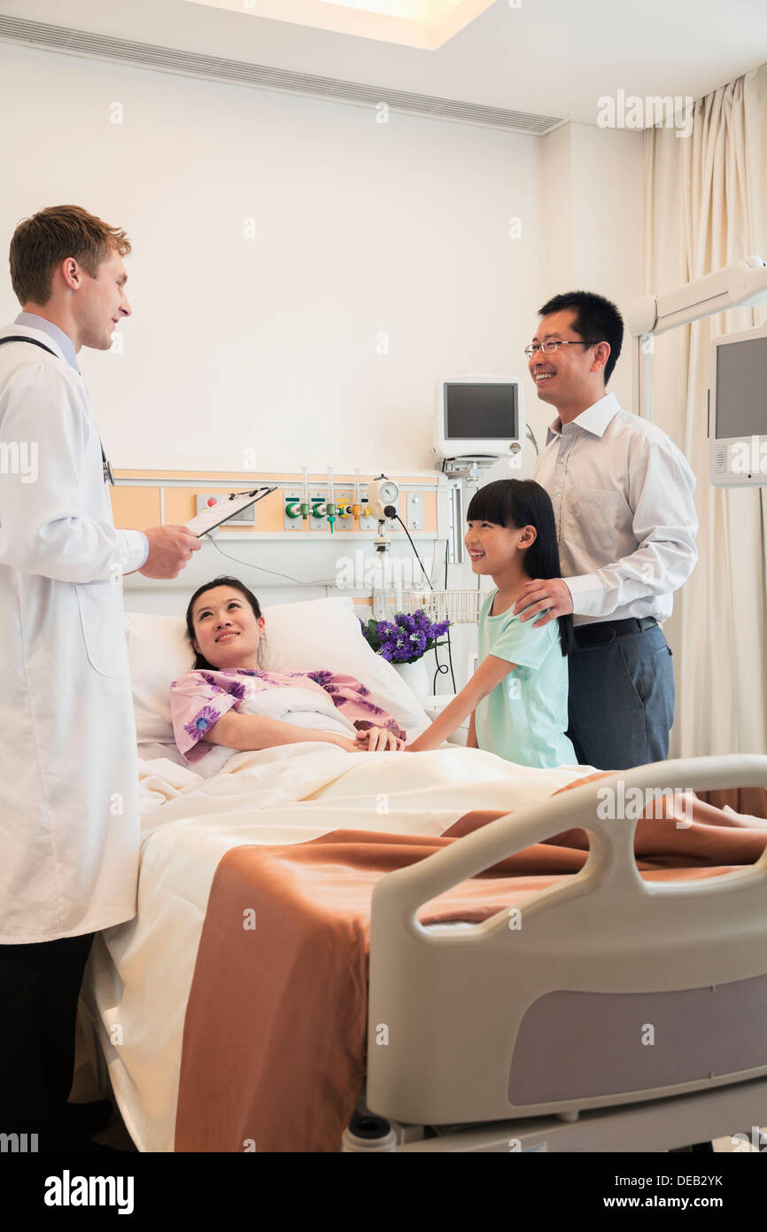 Family visiting the mother in the hospital, discussing with the doctor - Stock Image