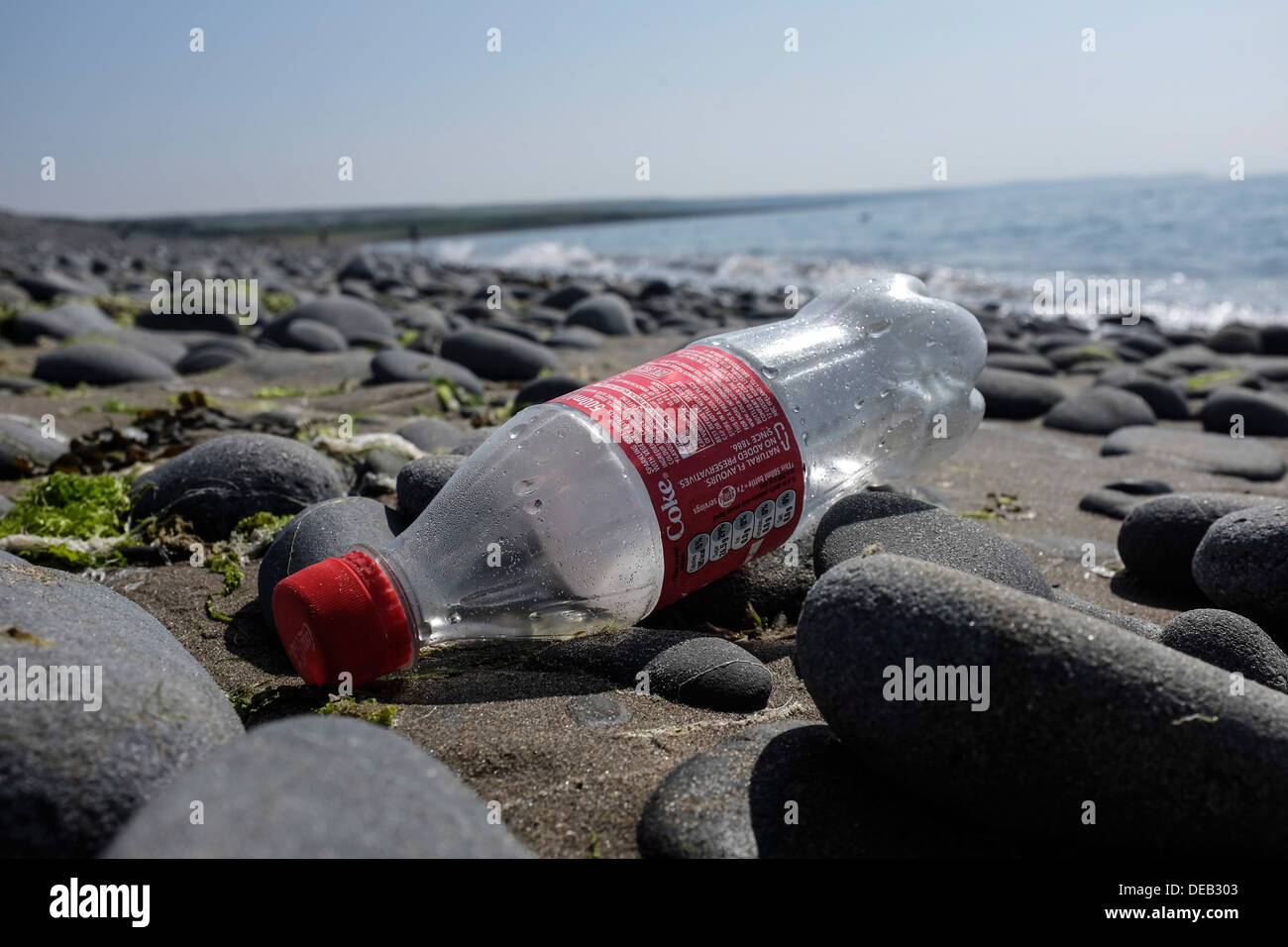 A discarded coca-cola coke soft drink  plastic bottle on Llanrhystud beach, Cardigan Bay coast, Ceredigion, west wales, uk - Stock Image