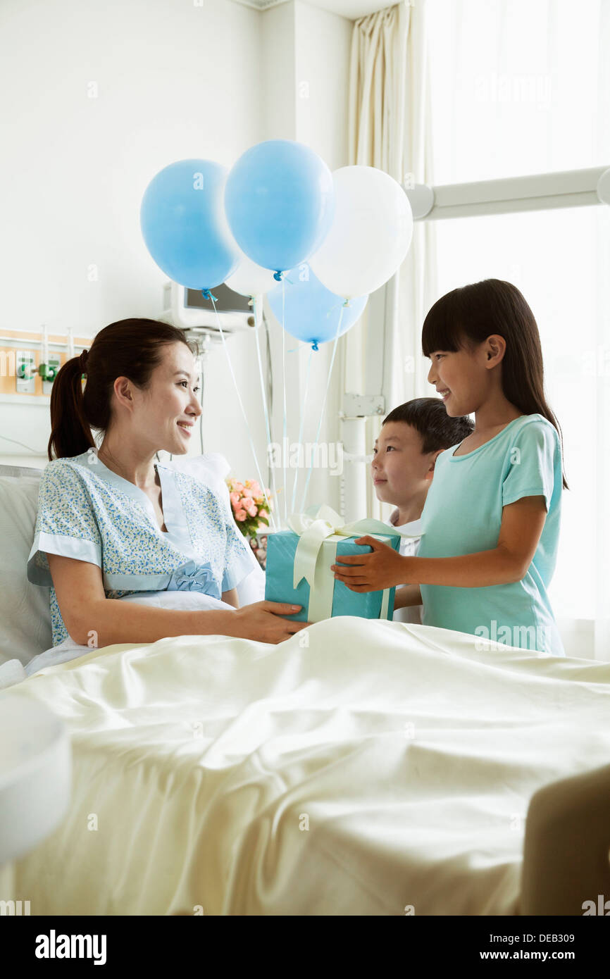 Girl and boy visiting their mother in the hospital, giving present and balloons - Stock Image