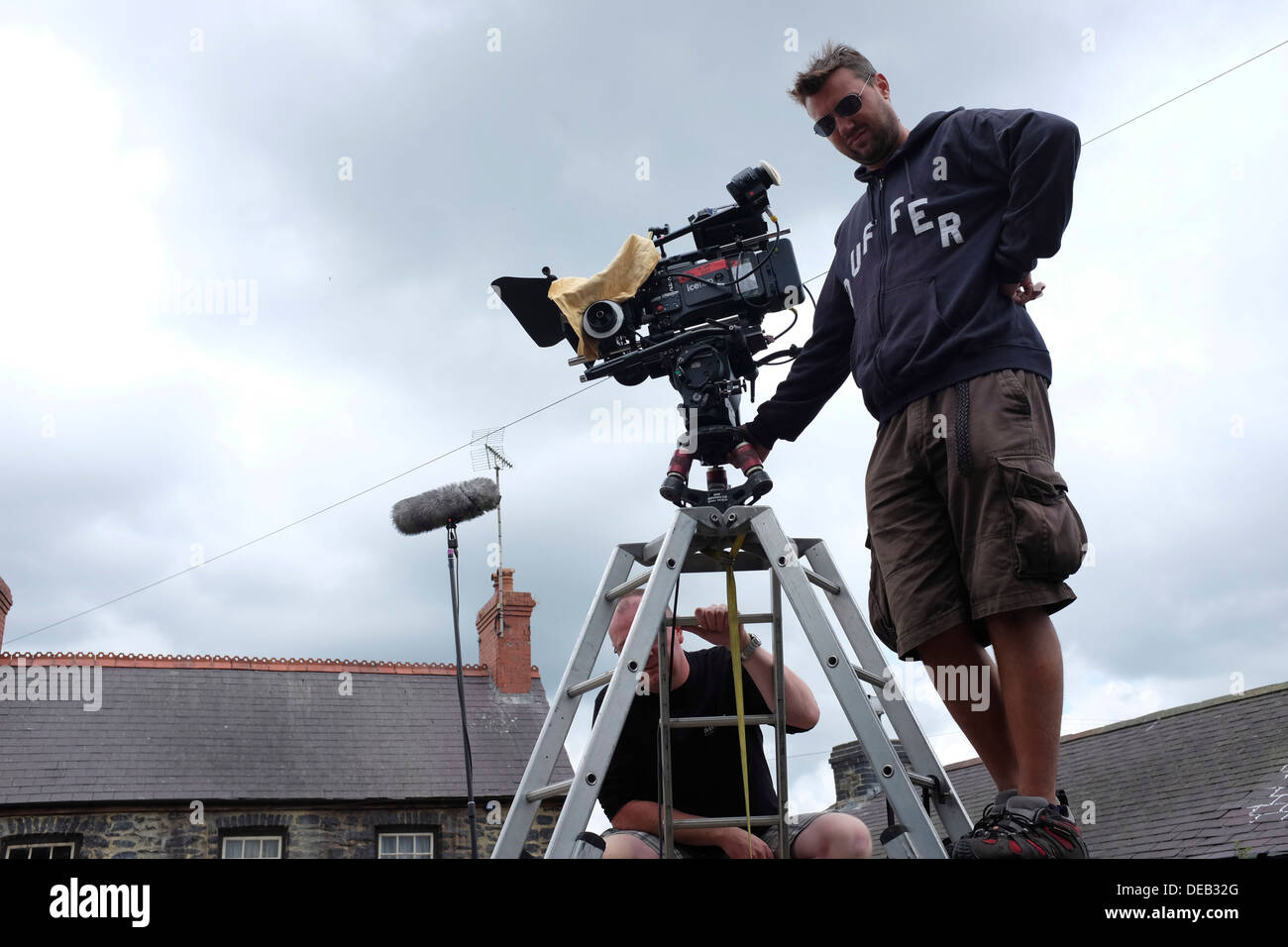 A cameraman standing on a high tripod ladder on a film location, UK - Stock Image