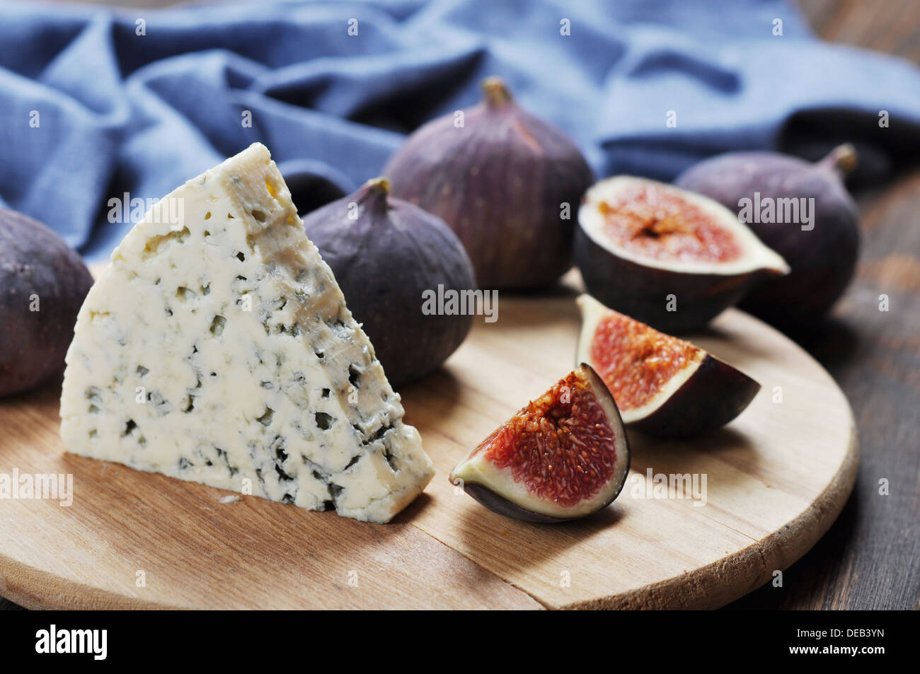 blue cheese and fresh figs fruit on a wooden cutting board - Stock Image