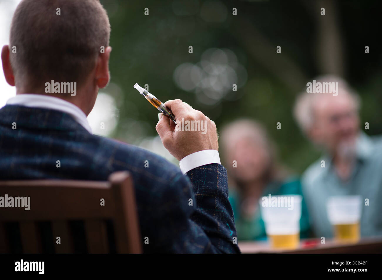 A man holding smoking  an electronic e-cigarette at an outdoor party UK - Stock Image