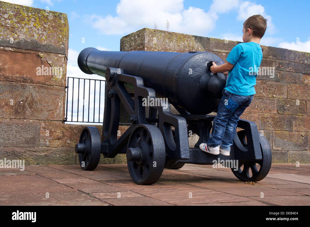 Boy on Canon at Carlisle Castle Carlisle Cumbria England United Kingdom - Stock Image
