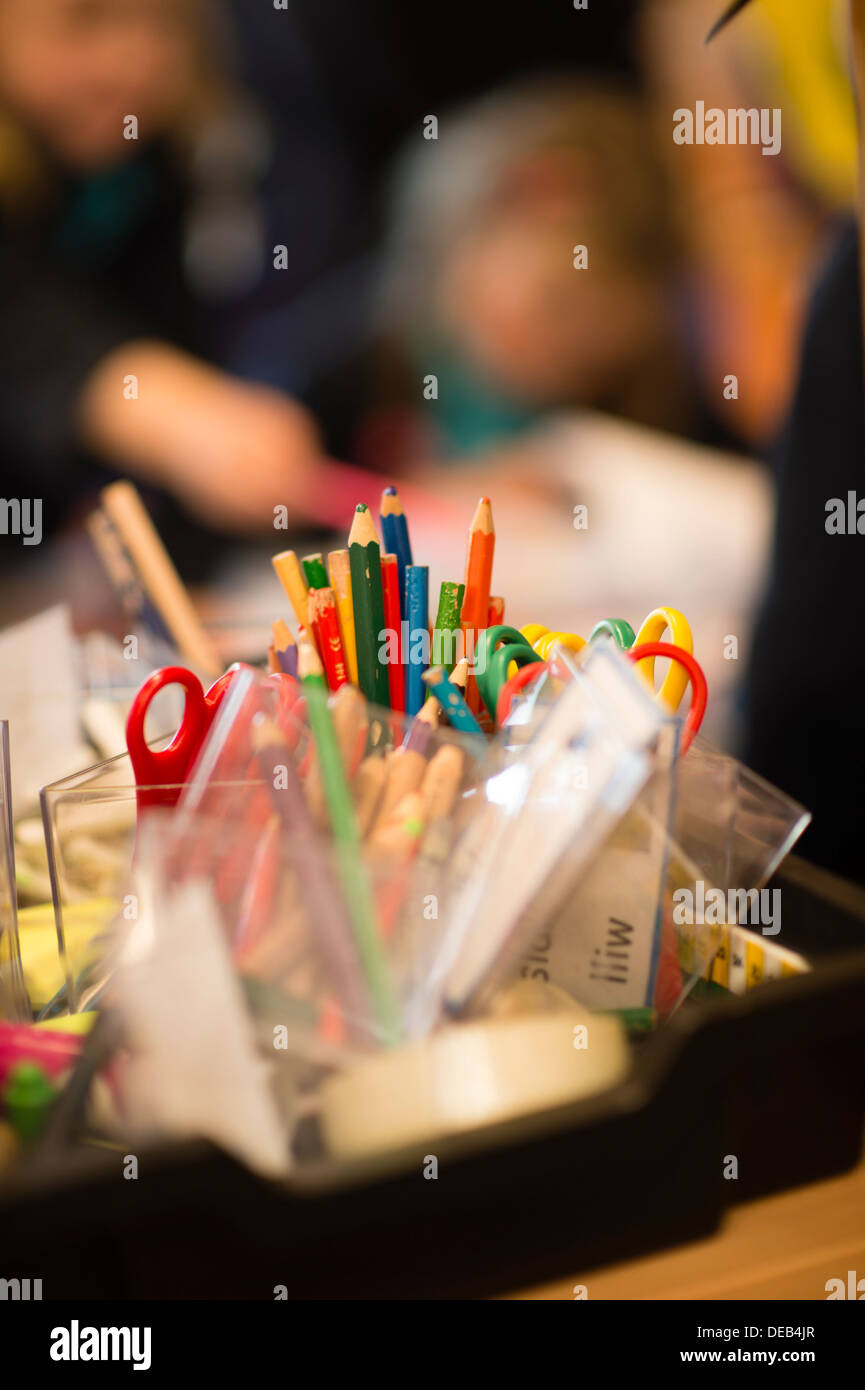 Pupils painting in an art class lesson in a primary school, Wales UK - Stock Image