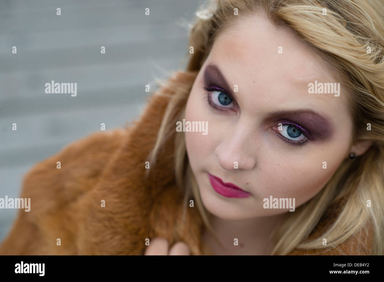 a young blond blonde woman teenage girl wearing a fur coat looking at camera with big eyes, UK - Stock Image