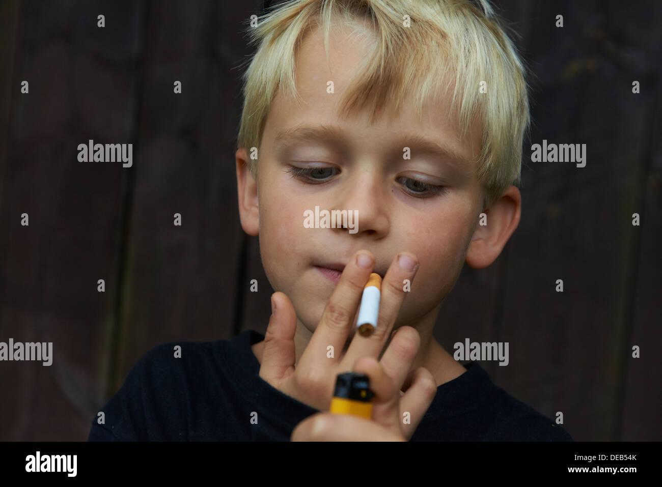 Child blond boy smoking cigarette wooden background alone