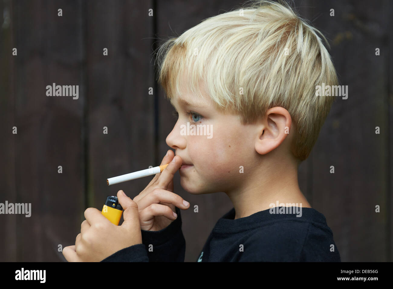 Child blond boy smoking cigarette young smoker stock image