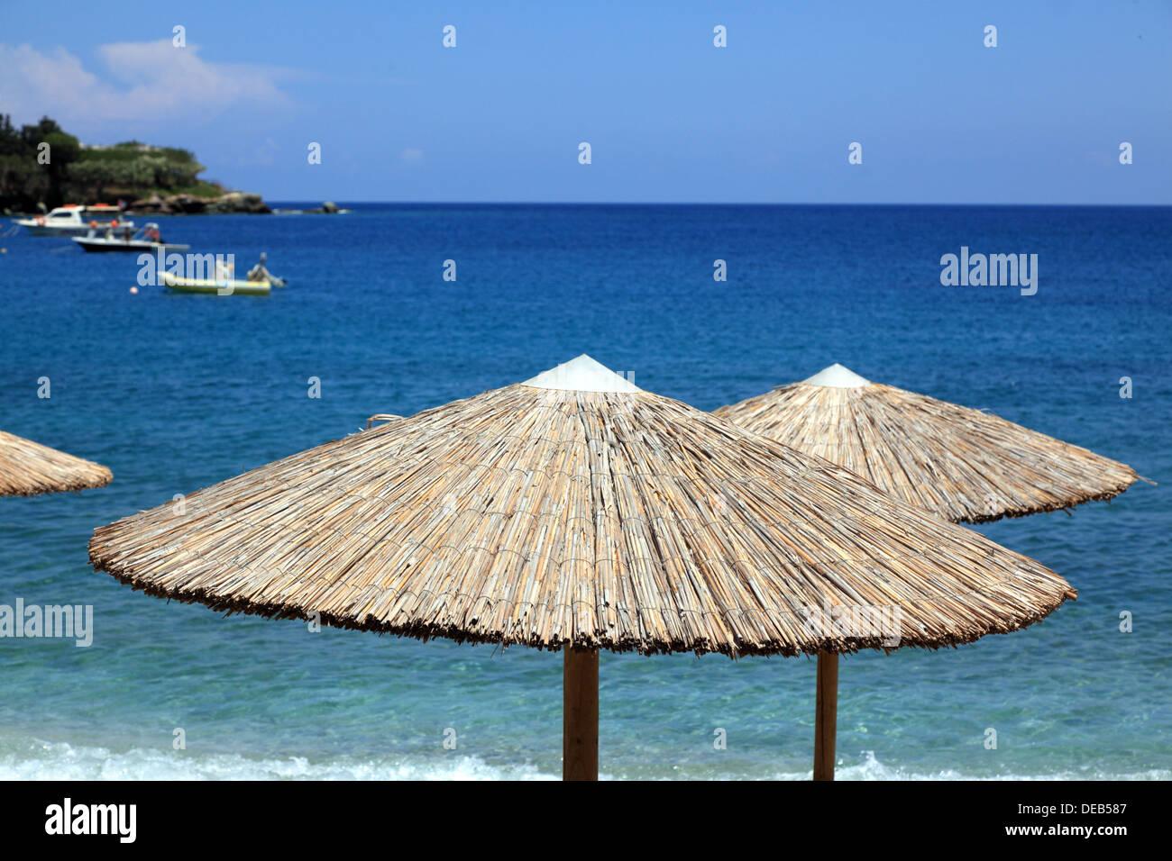 Straw umbrella on the beach. Agia Pelagia town, Crete Island, Greece - Stock Image