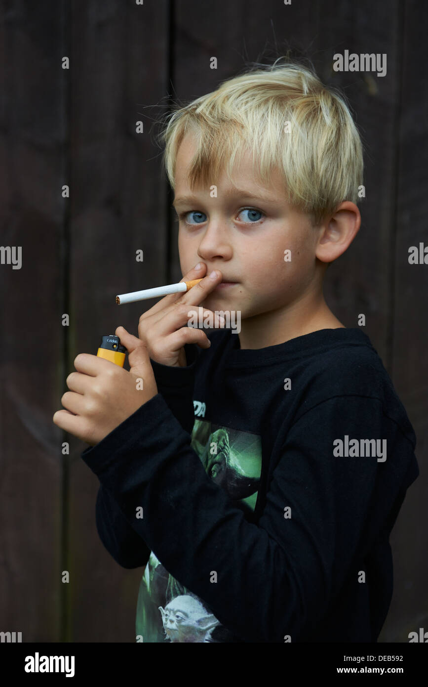 Child blond boy smoking cigarette stock image
