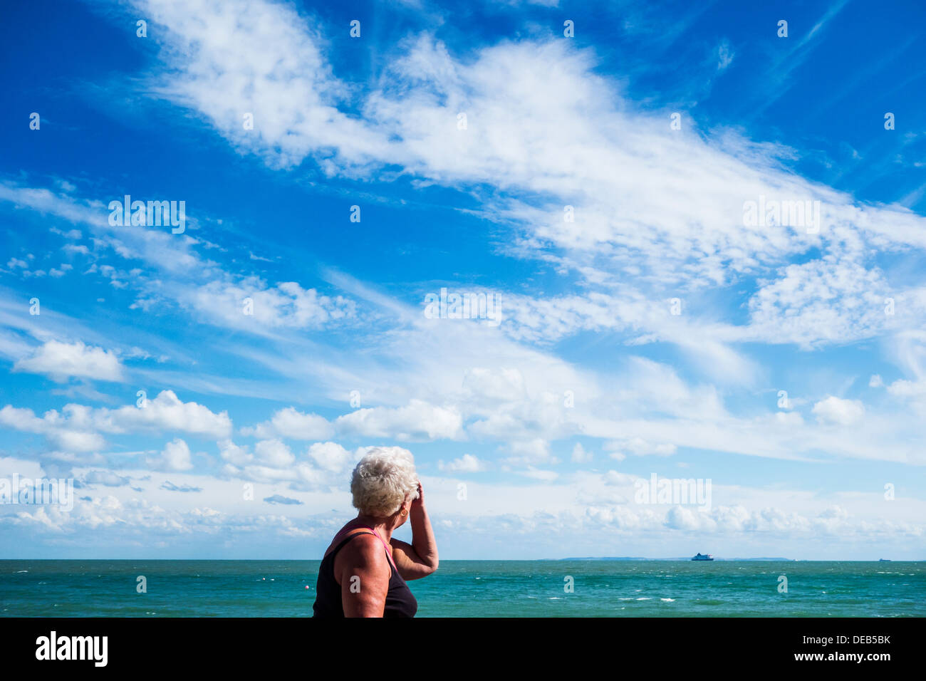 Elderly Pensioner Woman Walking Seaside Skyscape - Stock Image
