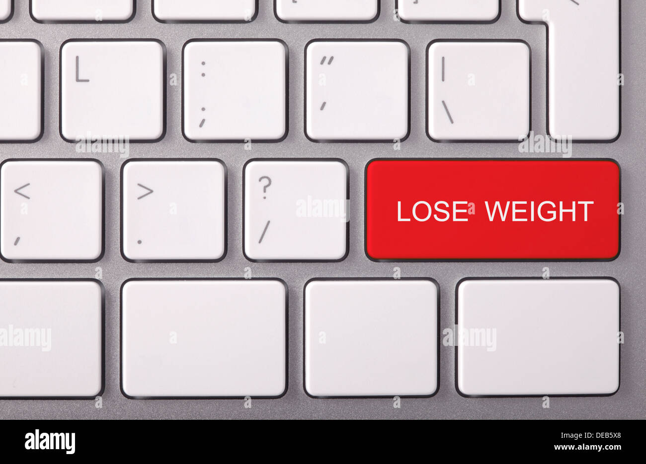 Laptop keyboard and red key 'LOSE WEIGHT' on it - Stock Image