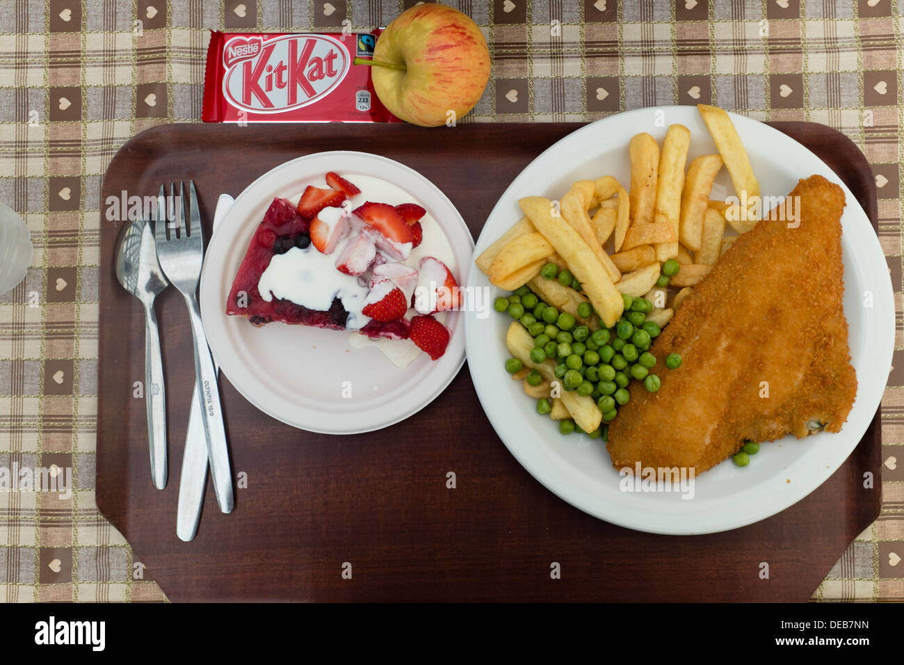 A plate of fish and chips and peas with a pudding and KitKat and apple on a tray, in a canteen, UK - Stock Image