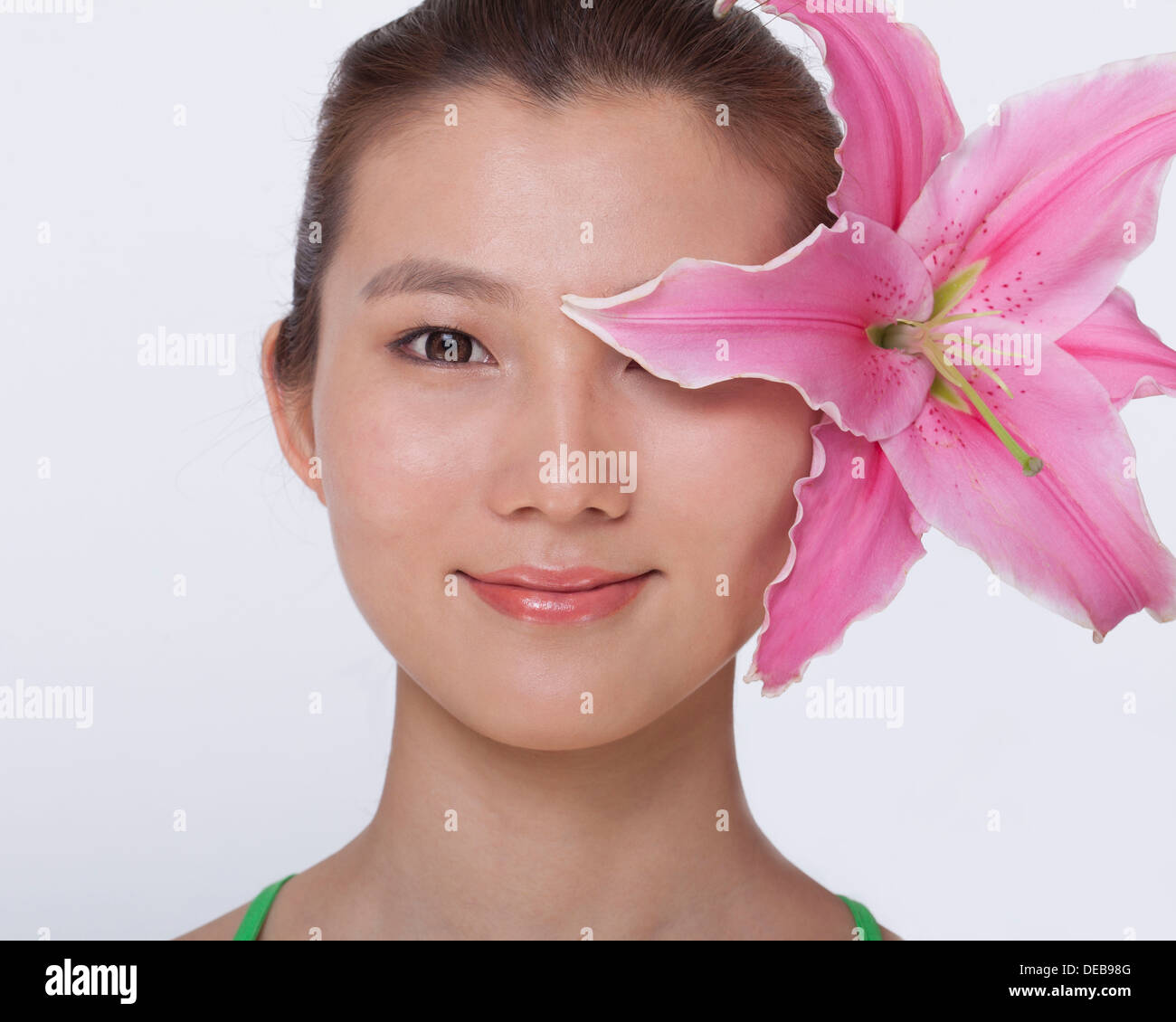 Portrait of young, smiling, beautiful woman with a large pink flower tucked behind her ear, studio shot - Stock Image