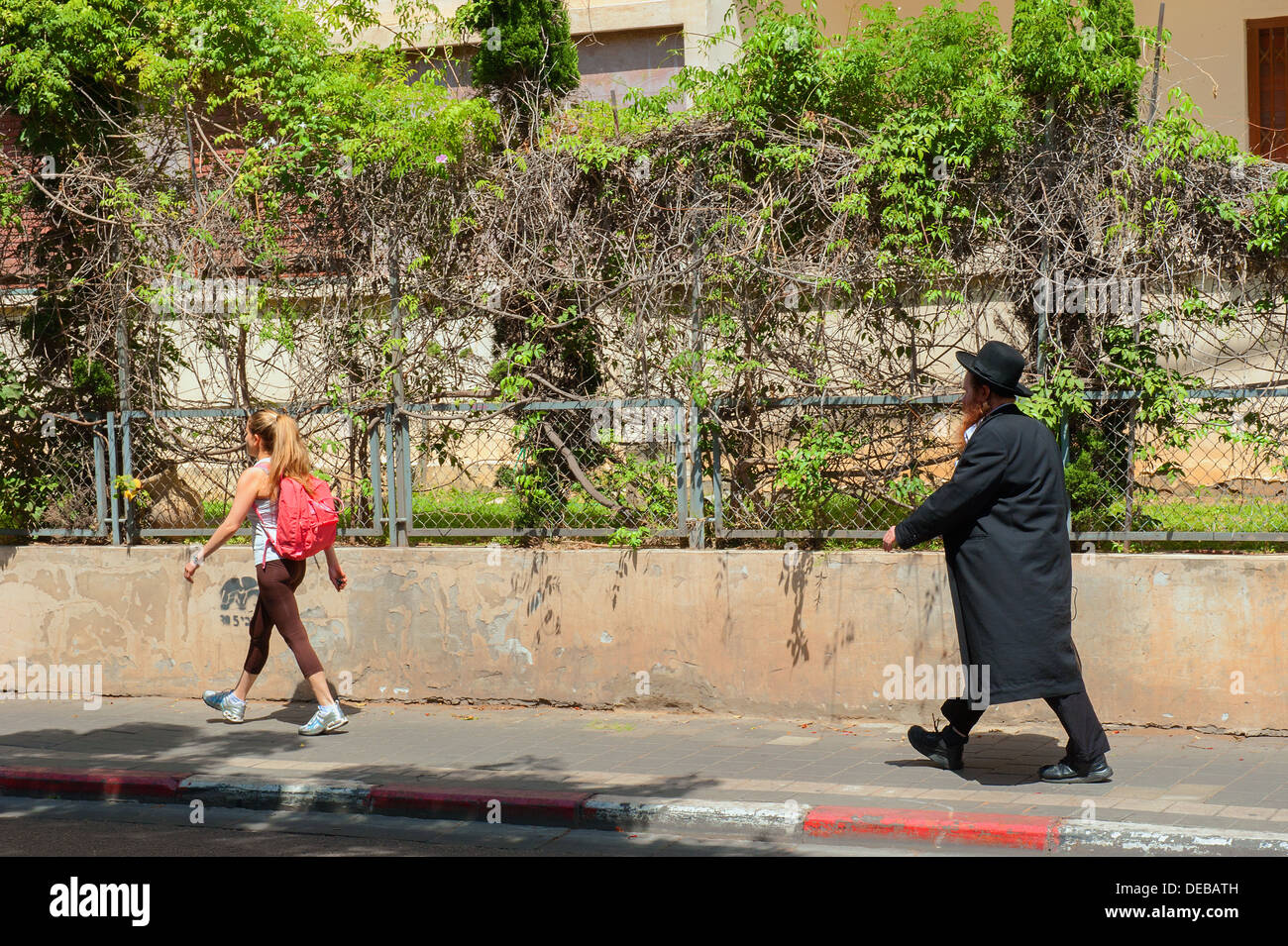An Orthodox Jew and a secular woman walking in Rothschild Boulevard, Tel Aviv, Israel - Stock Image