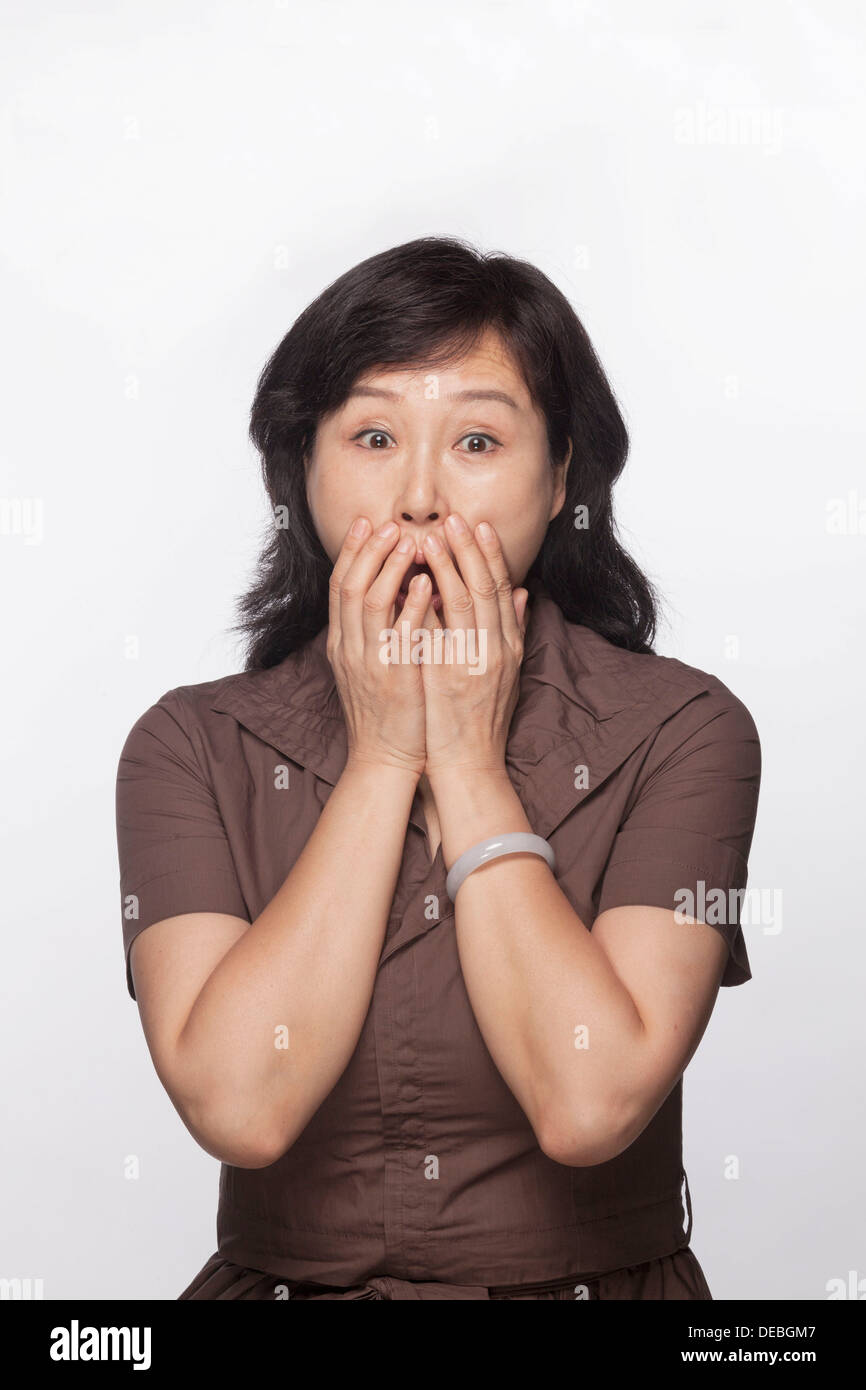 Portrait of shocked and surprised woman with hands covering her mouth, studio shot - Stock Image