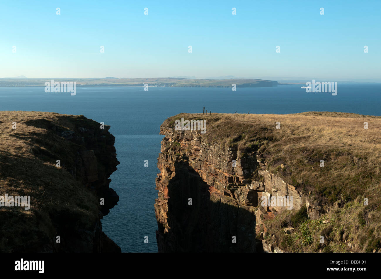 A geo (rock cleft) on Dunnet Head, near Thurso, Caithness, Scotland, UK. Holborn Head near Scrabster in the distance. - Stock Image
