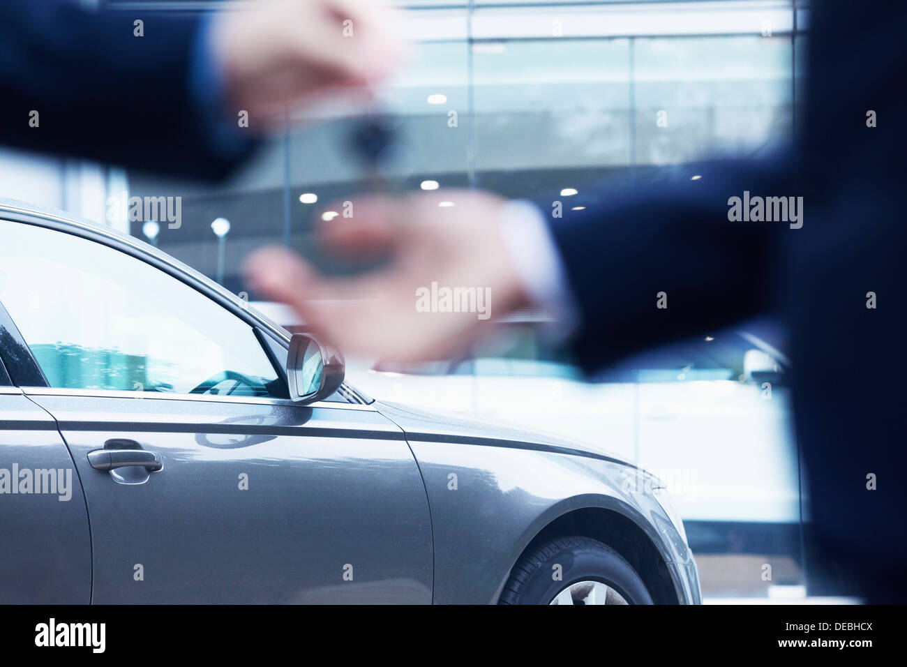 Car salesman handing over the keys for a new car to a young businessman, close-up - Stock Image