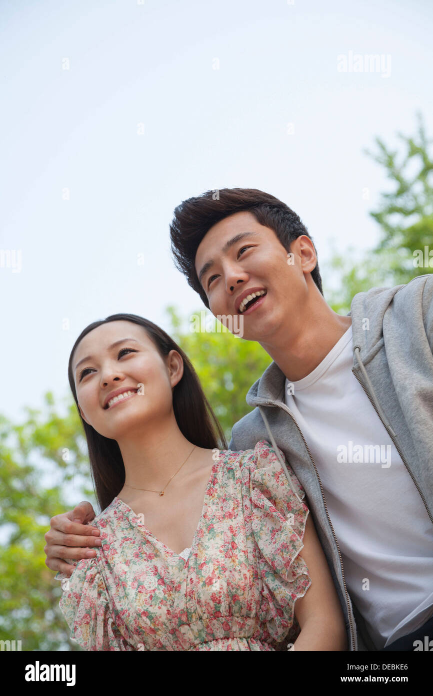 Smiling happy young couple with arm around the shoulders outdoors in a park, front view Stock Photo