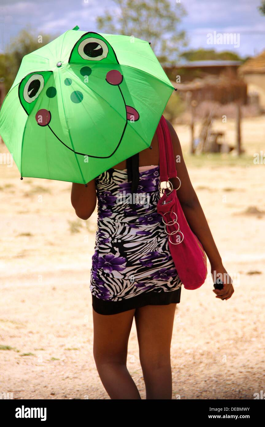 Young lady with a ´frog´ umbrella, Toteng, Botswana - Stock Image