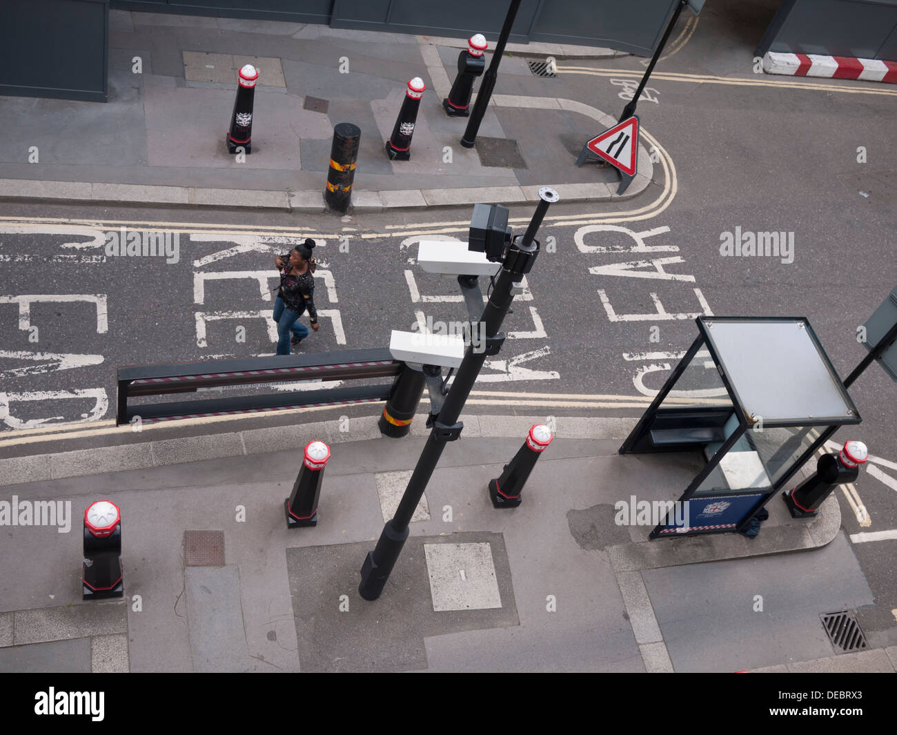woman walking past city of London UK  surveillance cctv cameras in street Stock Photo