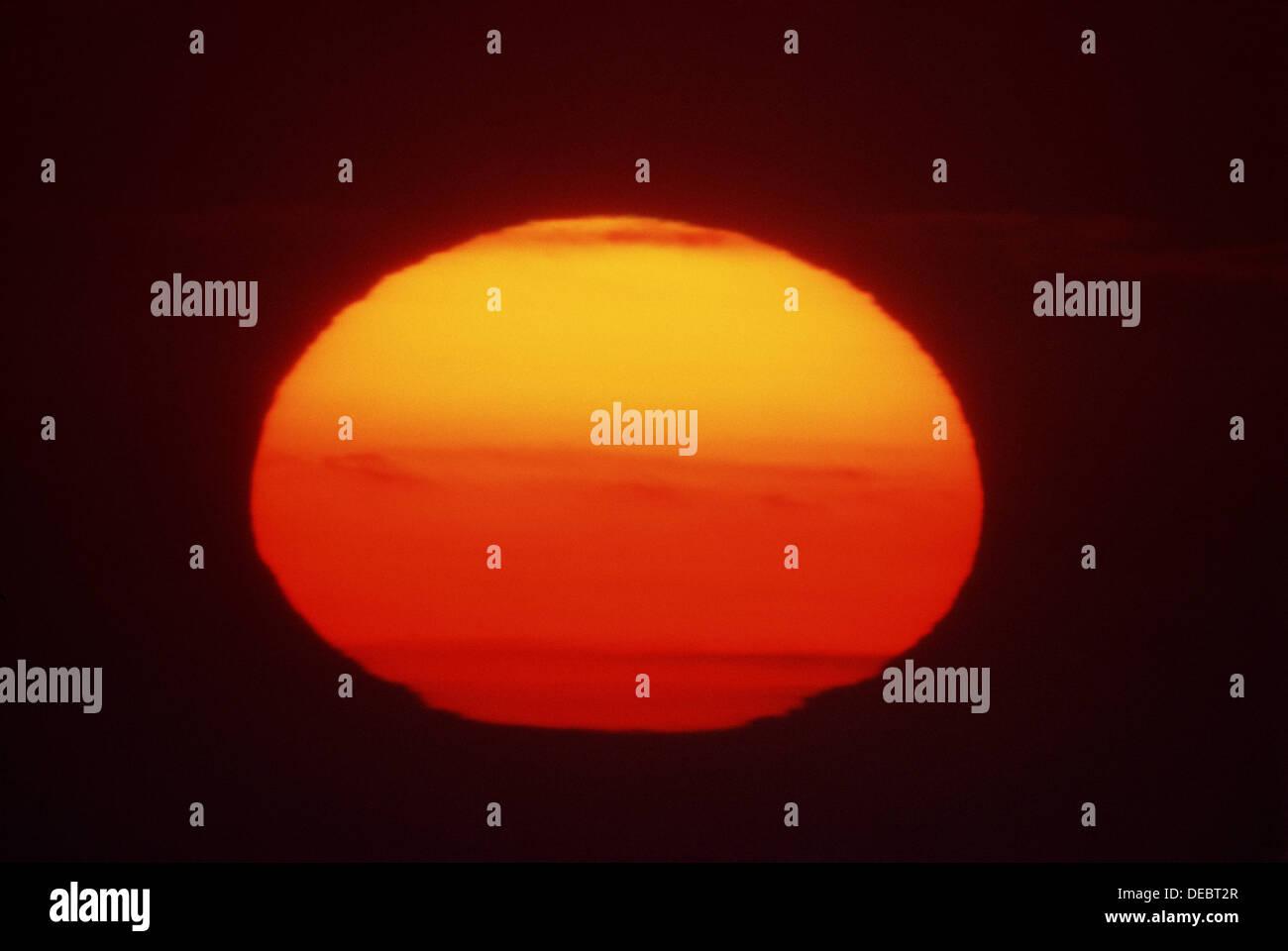 BRIGHT RED SUN IN DARK SKY - Stock Image