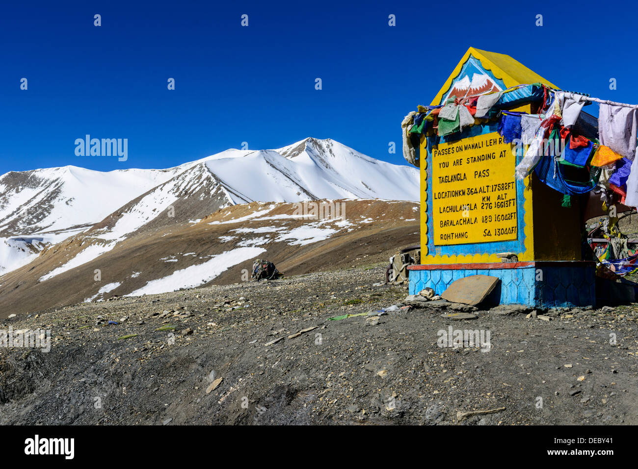 The milestone on top of Taglang La, 5.325 m, the highest pass on the Manali-Leh Highway, snow covered mountains in the distance - Stock Image