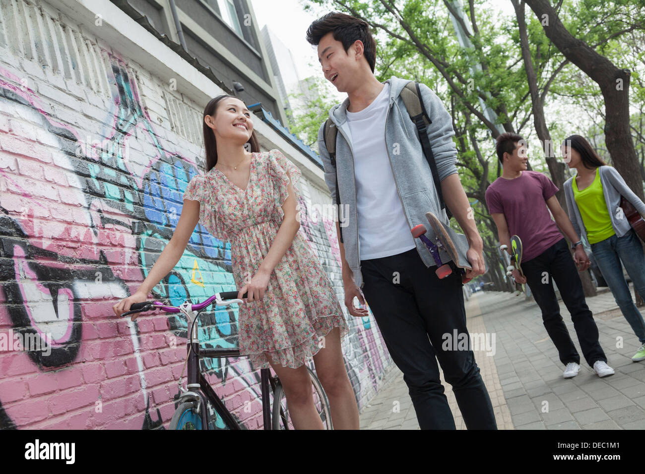 Two young couples walking down the street by a wall with graffiti, smiling and flirting with each other Stock Photo