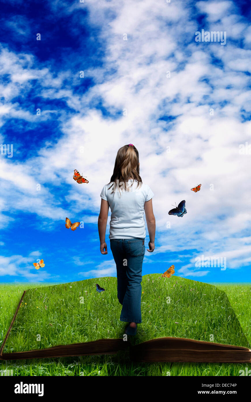 girl walking on a green book surrounded by butterflies, imagination, dream and creativity concept - Stock Image