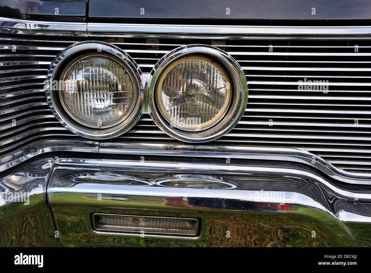 Close up of the radiator grille and headlights of an American car from the 1950s, isolated on white - Stock Image