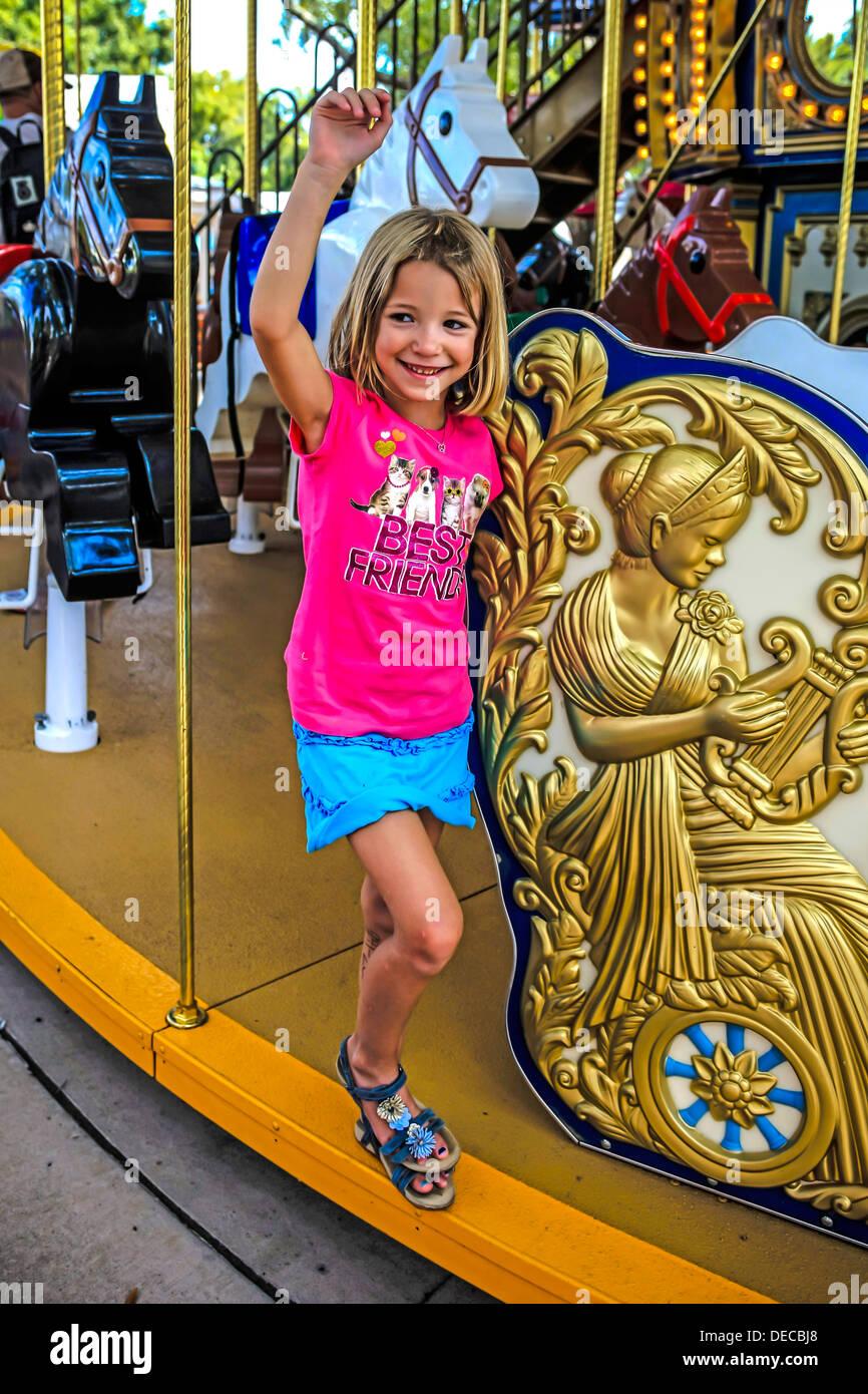 Young girl enjoys a ride on a carousel at the Legoland Theme Park Florida Stock Photo