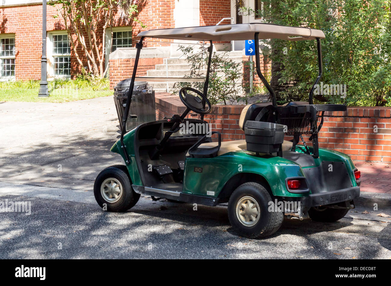 Electric EZGO powered golf cart, dark green with black trim cream coloured top and upholstery. - Stock Image