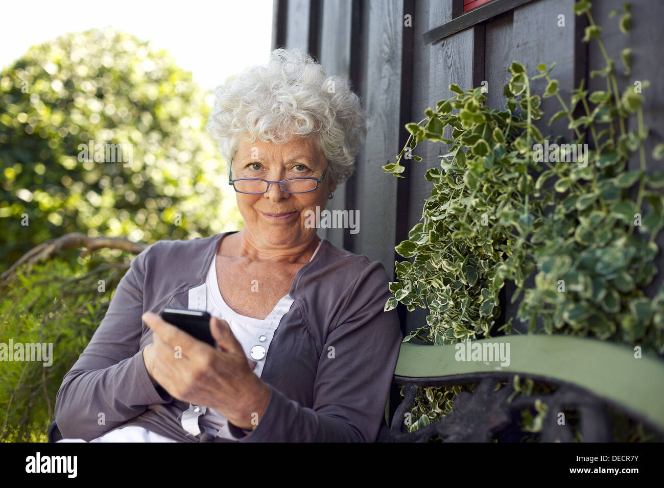 Senior woman using a mobile phone while sitting on bench in her backyard garden - Stock Image