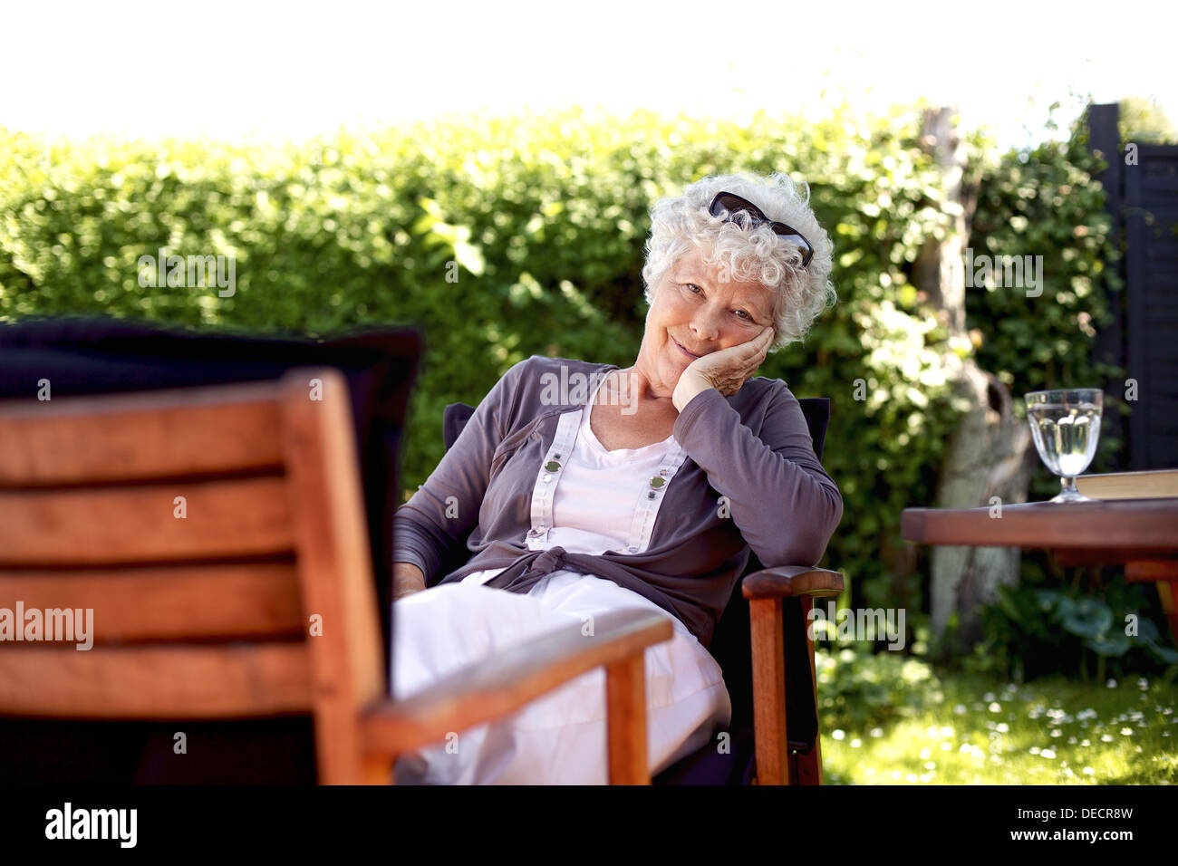 Old woman sitting on chair looking at camera. Senior female relaxing in backyard garden enjoying her retirement days - Stock Image
