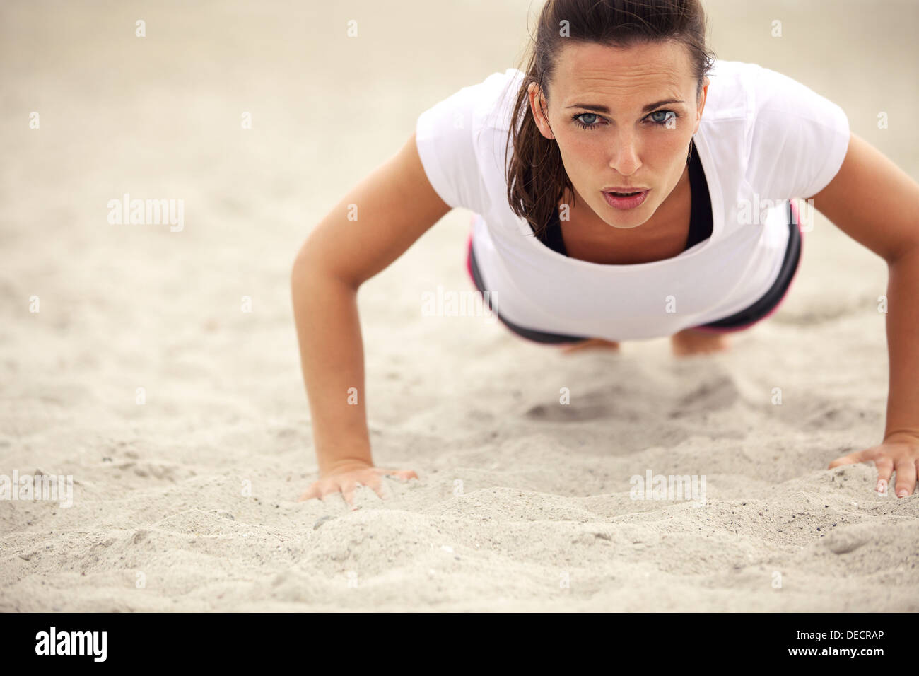 Push-ups fitness woman doing pushups outside on beach. Fit female sport model girl training crossfit outdoors. Caucasian athlete - Stock Image