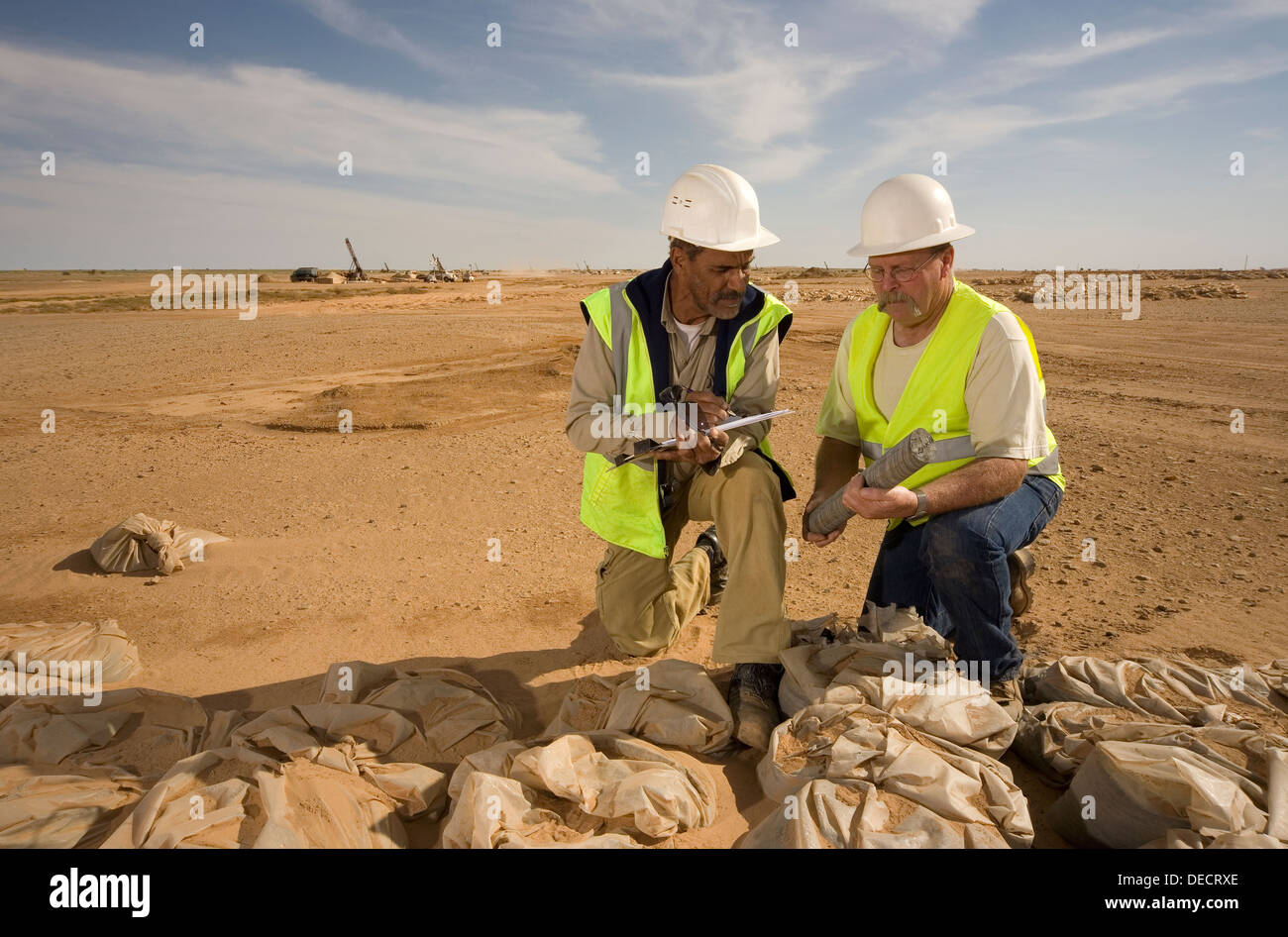 Geologists on surface gold mine examining core and grade samples from exploration drill rigs seen behind, Mauritania, NW Africa - Stock Image