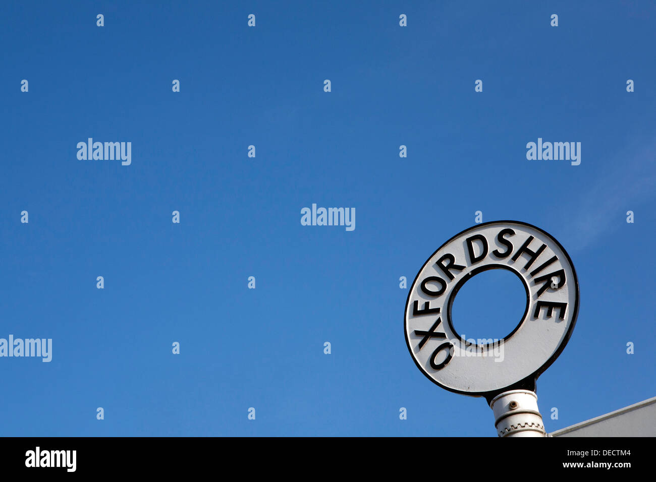 An old Oxfordshire cast iron road sign against a blue sky. - Stock Image