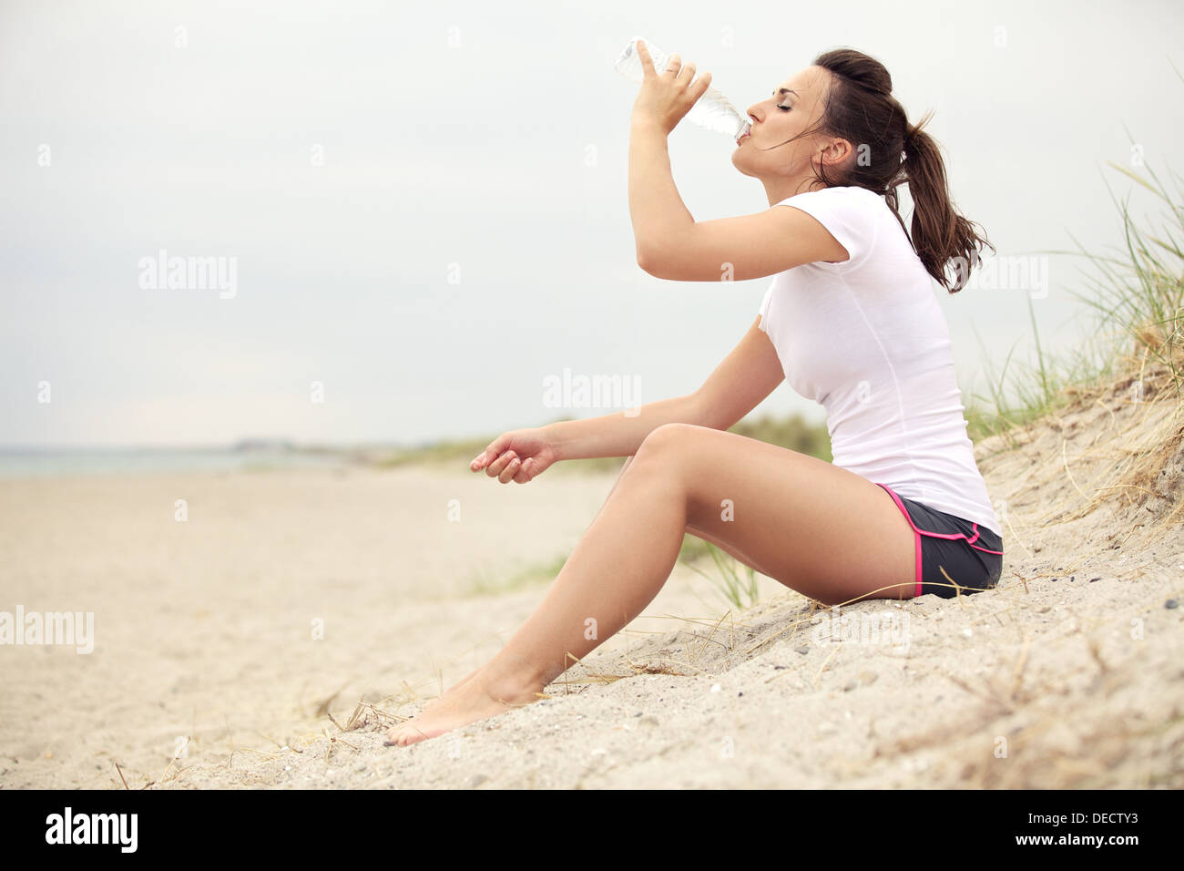 Active fitness woman at the beach drinking water from bottle. - Stock Image