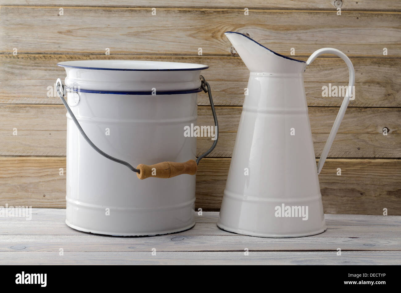A simple rustic, retro bathroom scene with enamel jug, bowl on a dilapidated old wooden cabinet Stock Photo