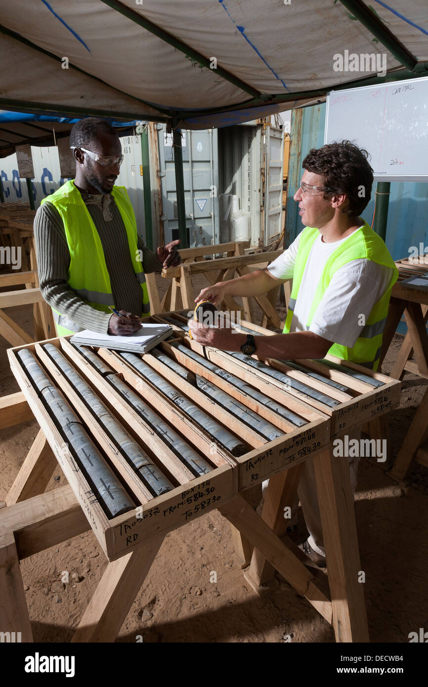 Technical logging and measuring of core samples in core shed by exploration geologists, surface gold mine, Mauritania, NW Africa - Stock Image