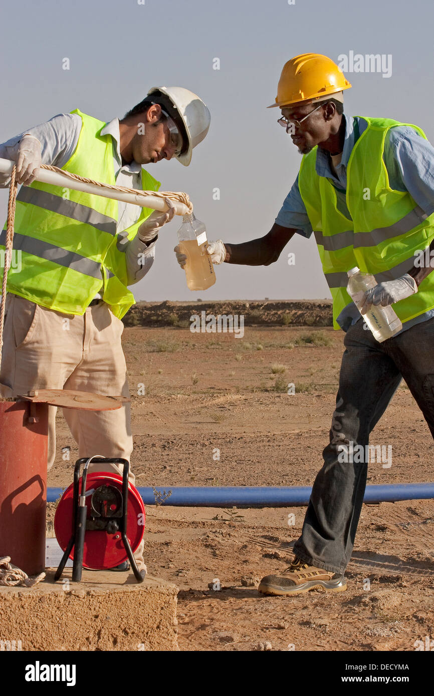 Taking water samples from bore hole, to test quality on industrial gold mining complex, Mauritania, NW Africa - Stock Image