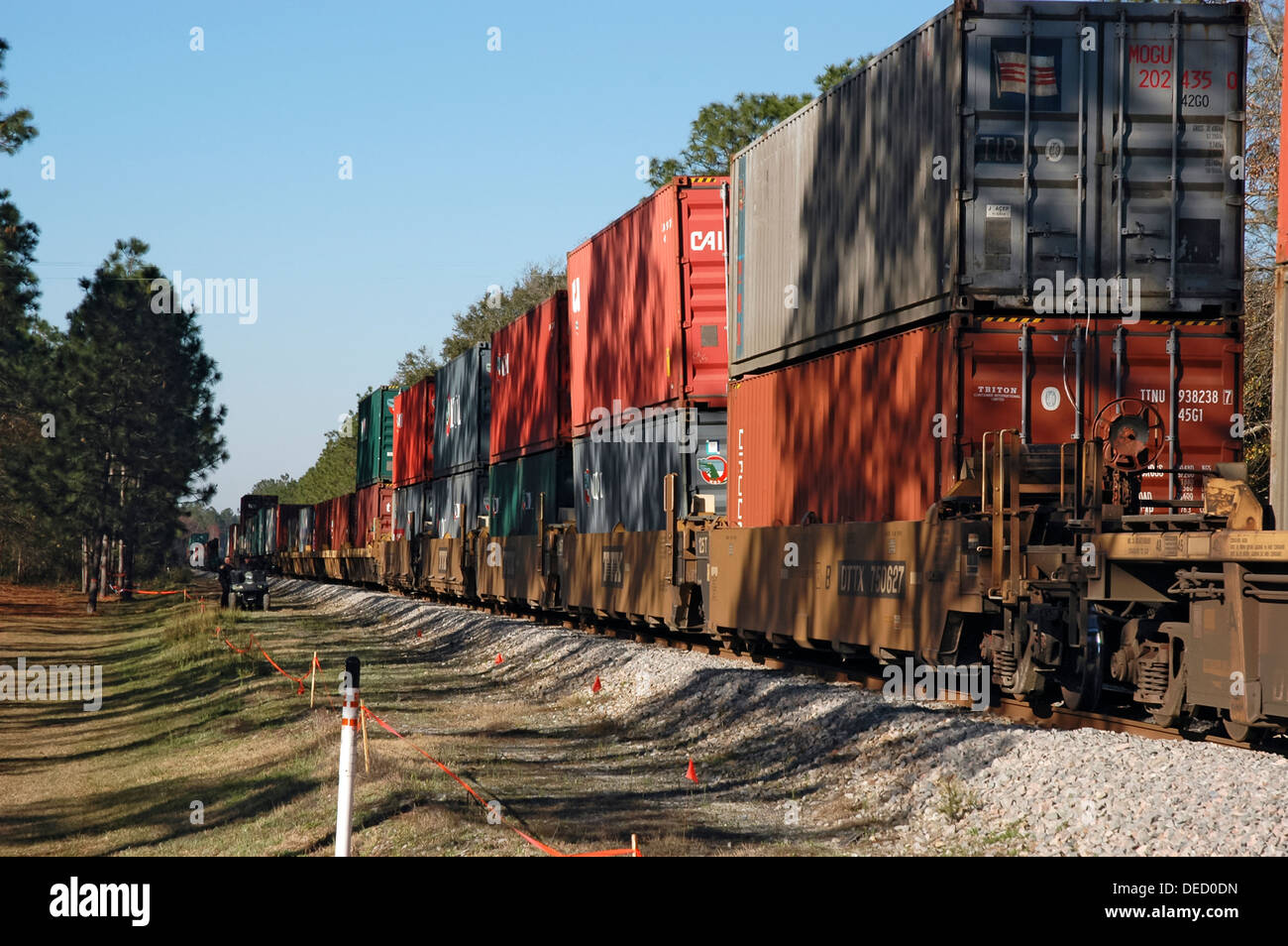Train carrying freight containers chugs through a rural area of North Florida. - Stock Image