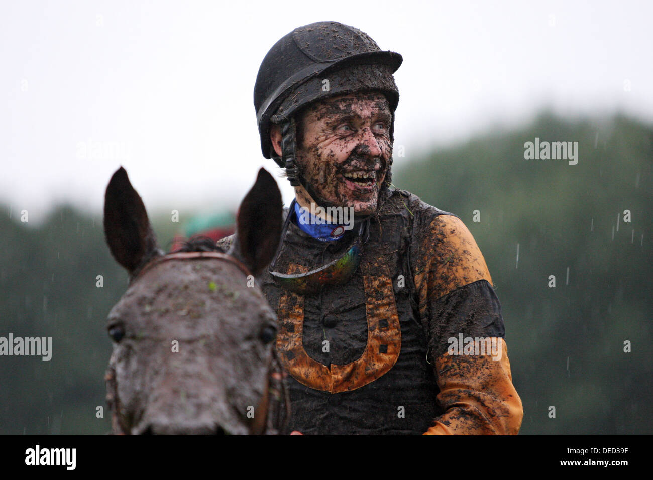 Hannover, Germany, Jockey laughs with dirt smeared face at the races - Stock Image