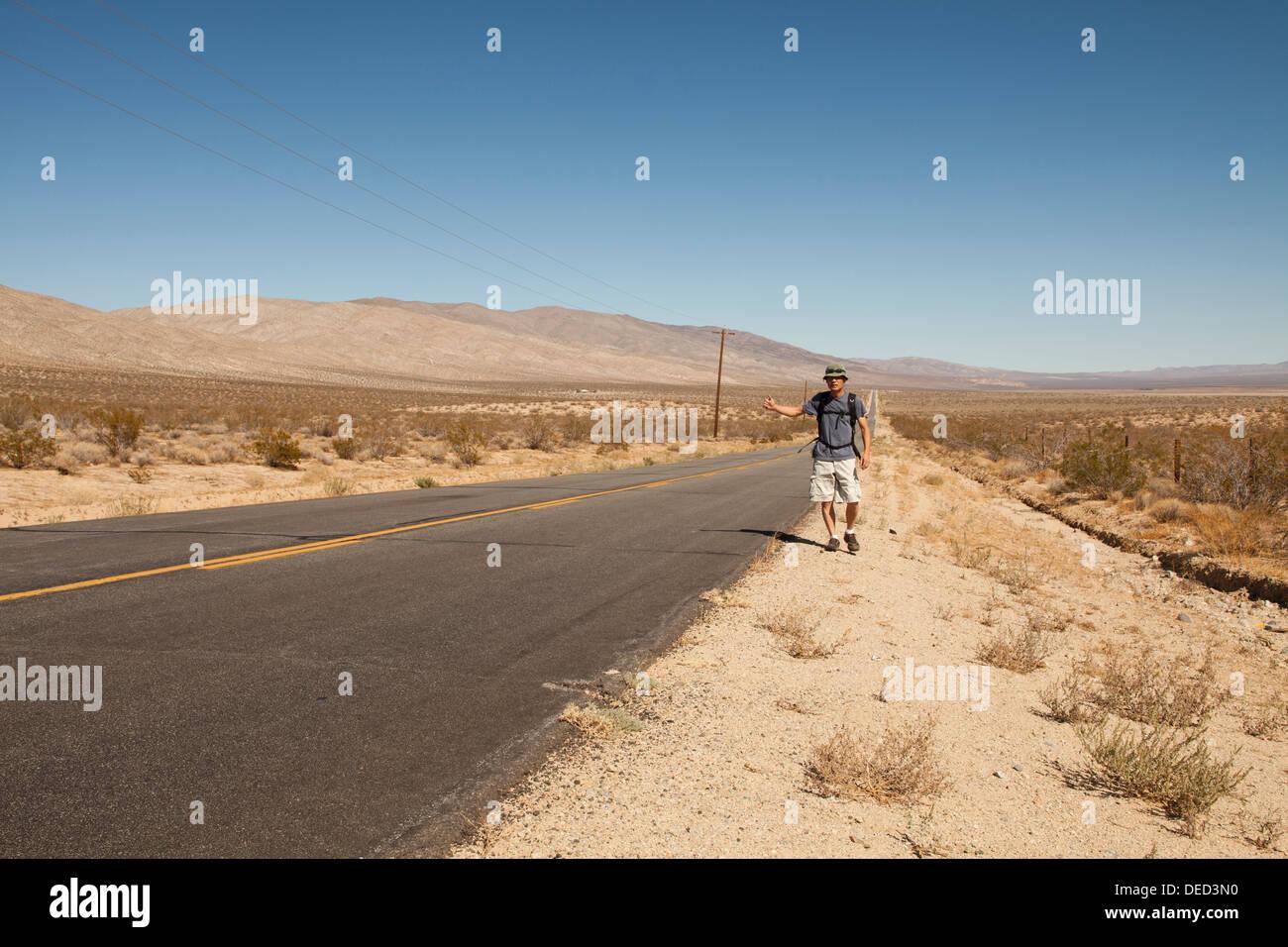 Man hitchhiking on a rural desert road - California USA - Stock Image