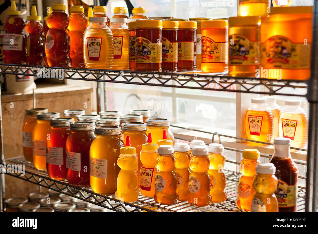 Honey bottles on shelf - Stock Image