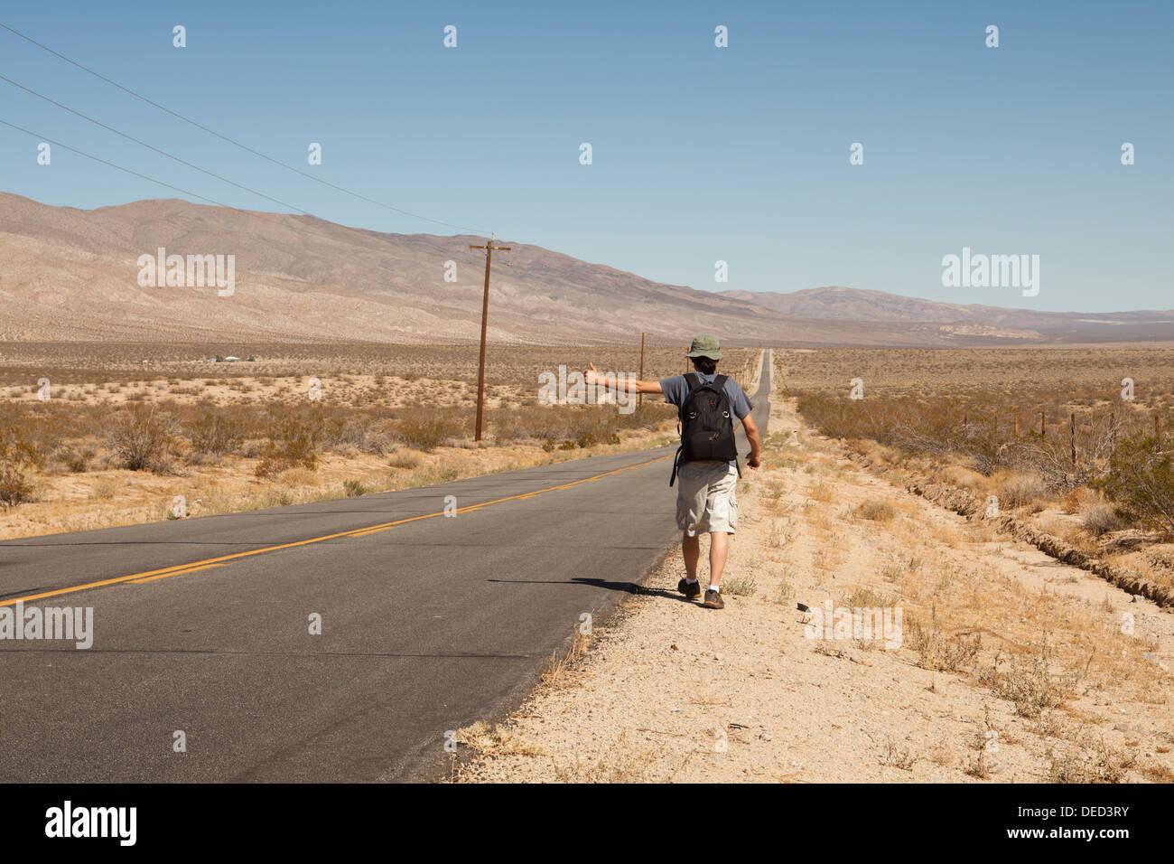 Man hitchhiking on a rural desert road - California USA Stock Photo
