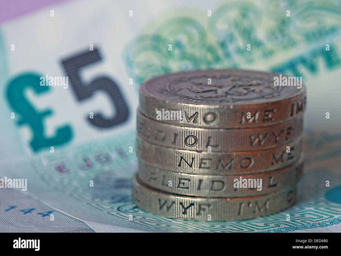 British Sterling Pound coins stacked spelled 'Money', sitting on a UK Fiver - Stock Image