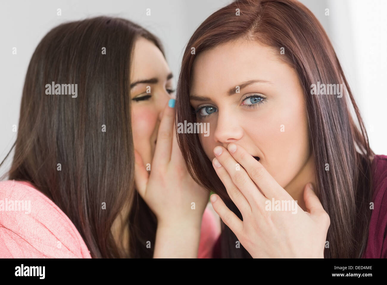 Two young girls sharing secrets - Stock Image
