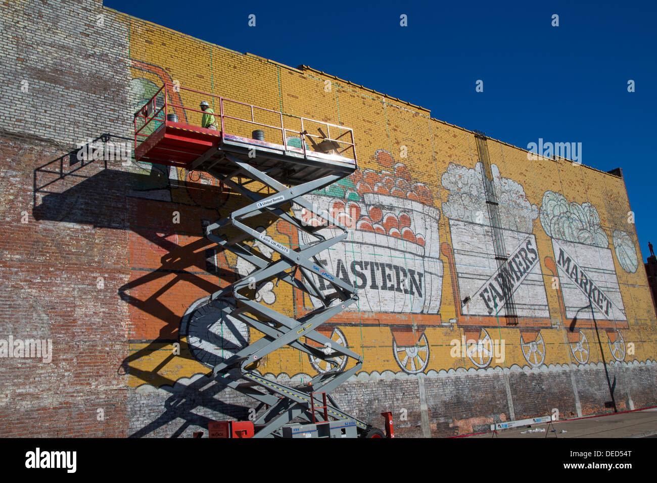 Detroit, Michigan - A worker repairs the painting on a wall at Eastern Market, the city's major farmers' market. - Stock Image