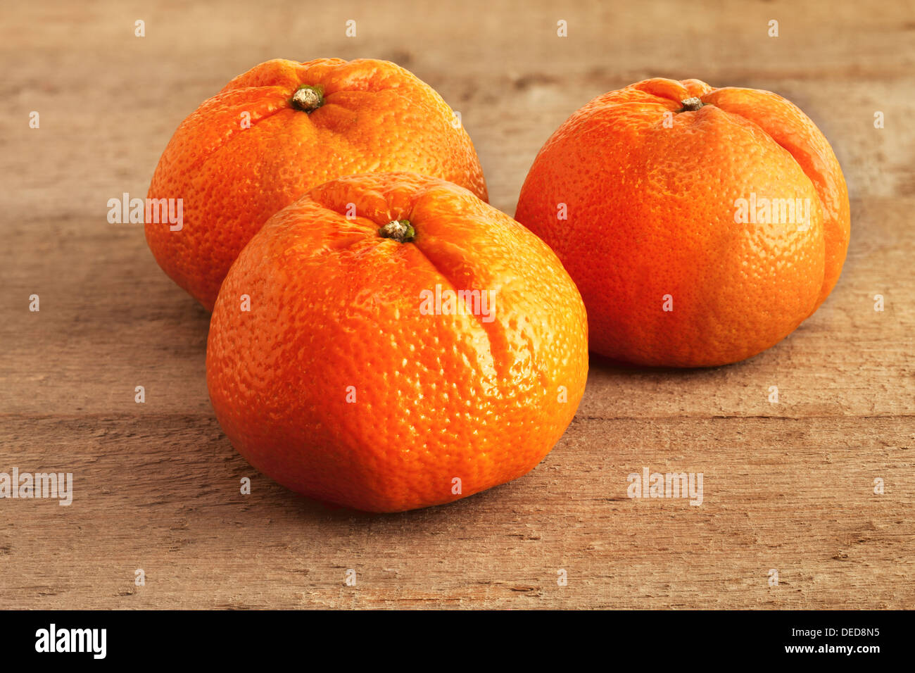Mandarin Oranges - three mandarin oranges on a rustic wooden board. - Stock Image